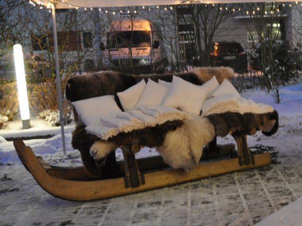 Riesenschlitten als Sofa mit Fellen und Kissen